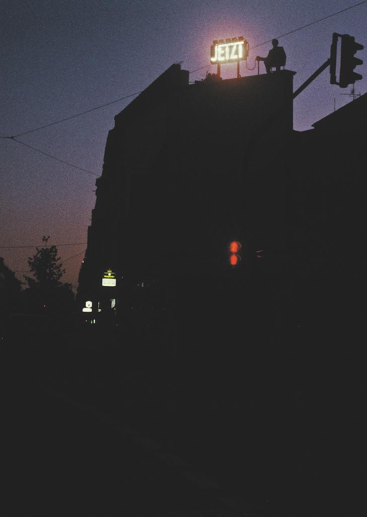 Christian Hasucha, JETZT, 1989, Dreiwöchige abendliche Performance mit Blitzlichtkasten (Gerüstsitz 300 x 250 x 150 cm) auf Fassadenkante in 15 m Höhe, Köln, Performer: Hans-Jörg Tauchert, Foto: Studio Hasucha, Berlin